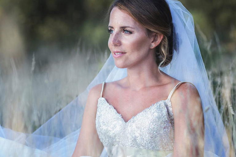 A beautiful boho bride sitting in the grass.