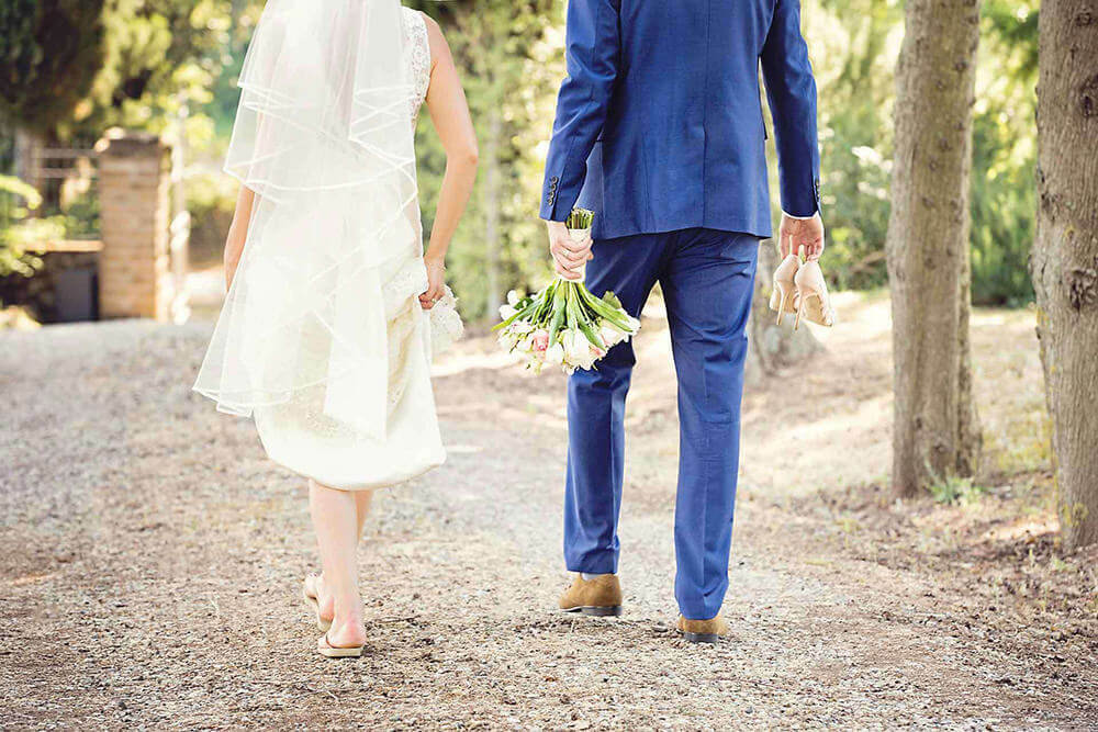 A bride and groom walking off in Tuscany. The groom is carrying the brides shoes and bouquet.