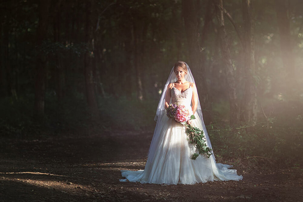 A stunning Bride poses in the sunlight in the woods.
