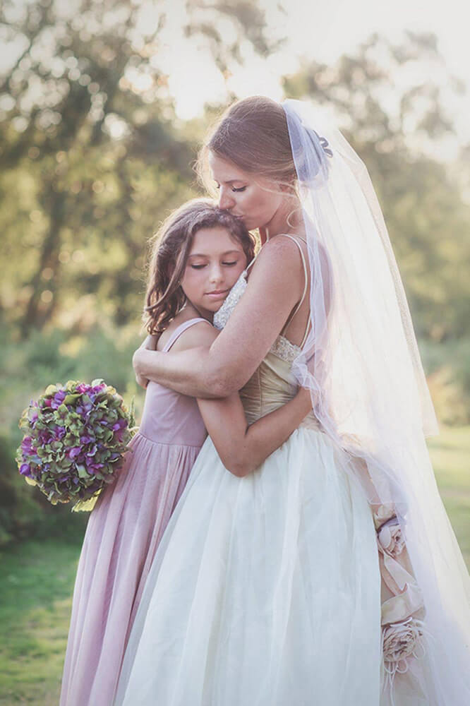 A bride embraces her daughter.