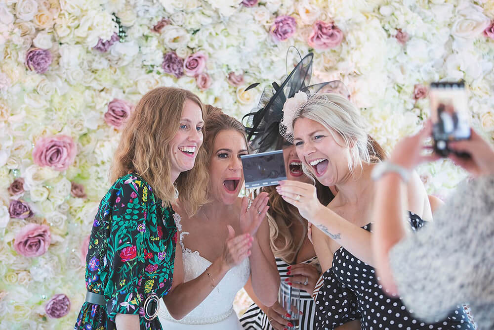 A bride and her girlfriends laughing at a photo at a wedding at Parley Manor, Christchurch.