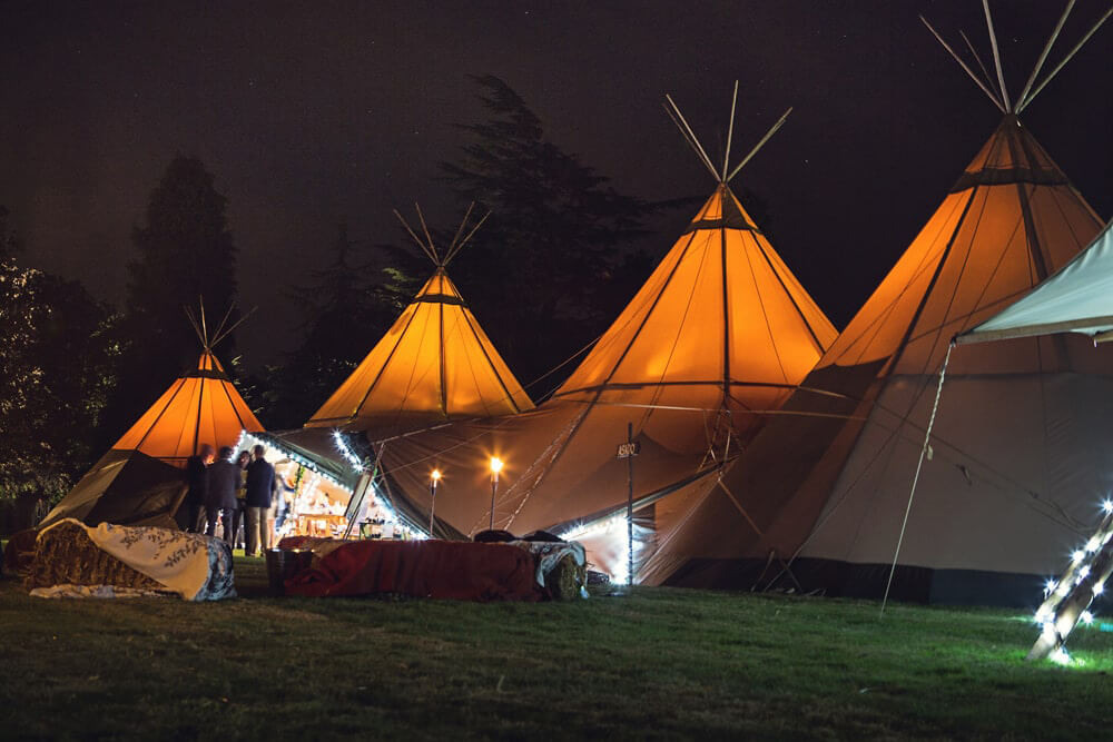Teepees lit up at night at a beautiful humanistic 1920s wedding in Henfield Sussex.